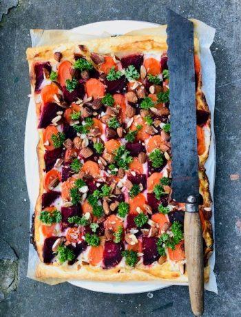 Een heerlijke en vegetarische plaattaart plaattaart rode biet, wortel en room van geitenkaas. Een super kleurrijke en vrolijke hartige taart waarmee je zeker vrolijke gezichten krijgt.