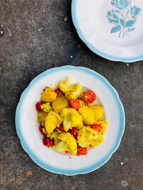 Een heerlijk en makkelijk vegetarisch en veganistisch eenpansgerecht, deze bloemkool, aardappel en tomaatjes uit de wok. Ideaal als vegetarisch hoofdgerecht op een doordeweekse dag.