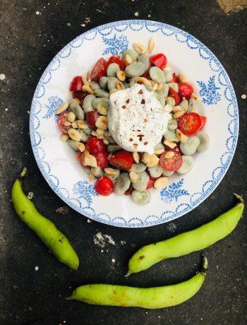 De verse tuinbonen in deze tuinbonen tomaten salade hebben niet meer nodig dan wat olijfolie, citroenrasp, cherrytomaatjes en verse burrata. Een heerlijke , eenvoudige en gezonde verse bonensalade.