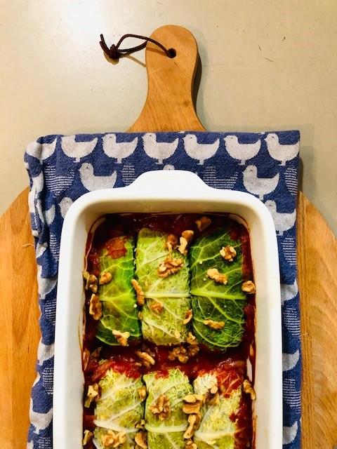 Zelfgemaakte vegetarische gevulde koolrolletjes van savooiekool of groene kool in tomatensaus. Gevuld met noten, champignons en rijst. Een mooie en lekkere vegetarische maaltijd.